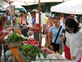 people shop for vegetables at a farmers market stand