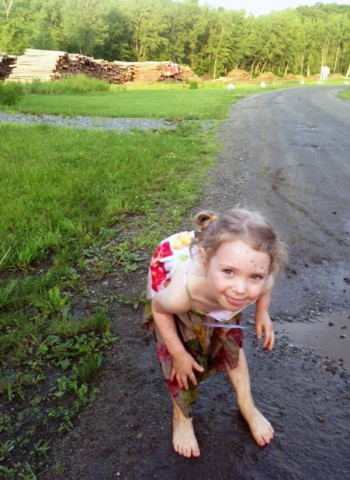 Young girl playing in the mud